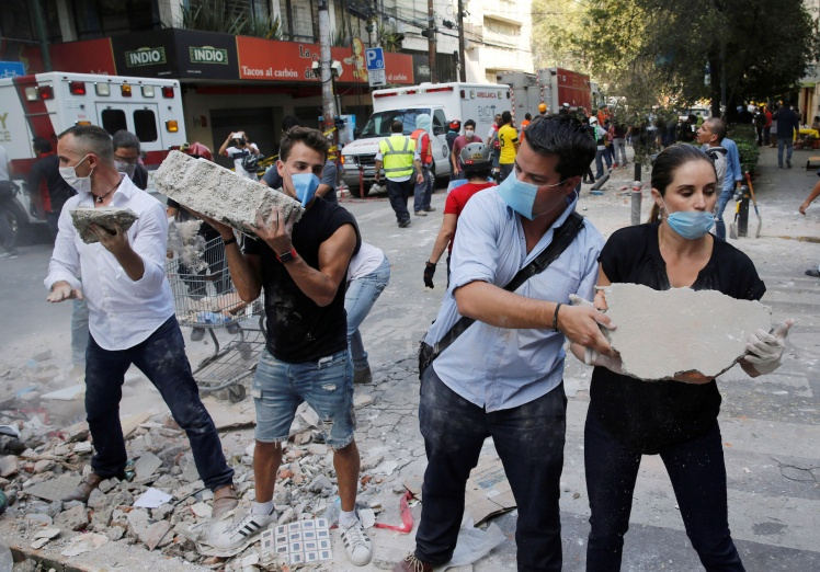 People remove debris outside at a collapsed building after an earthquake in Mexico City
